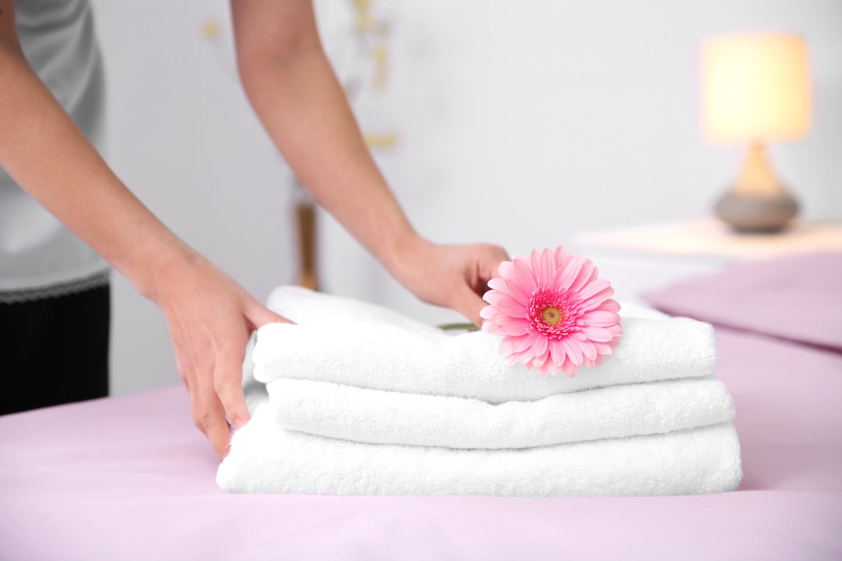 woman laying flower on folded towels