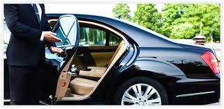 man holding open car door of luxury car