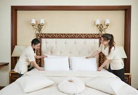 two housekeepers making a king bed