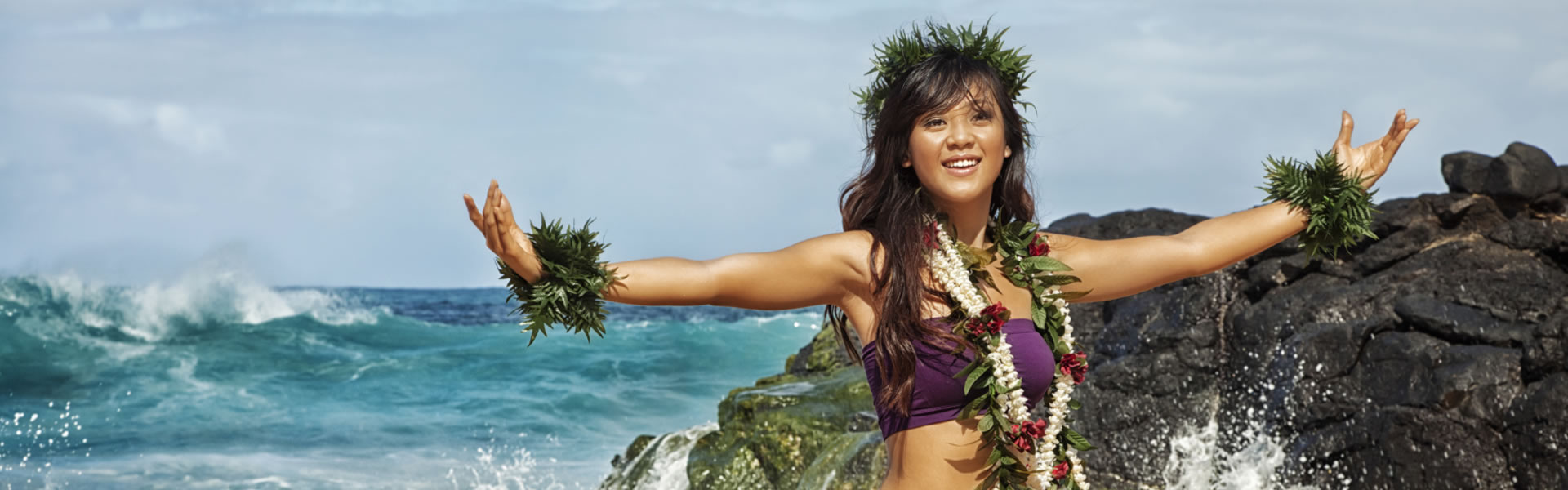 Woman wearing hawaiian skirt and head dress with ocean in background